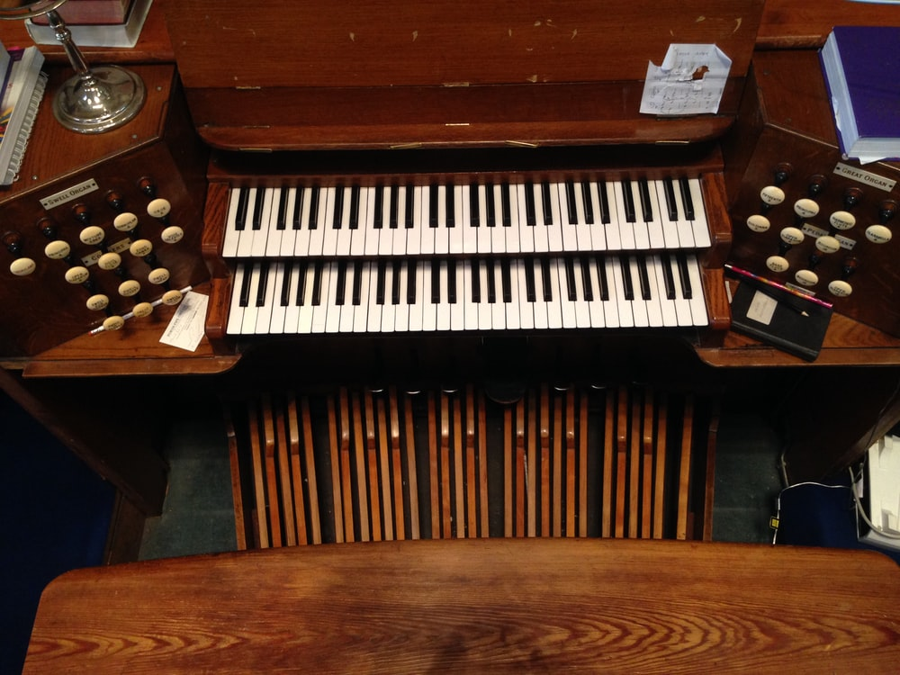 brown wooden upright piano with black and white piano keys