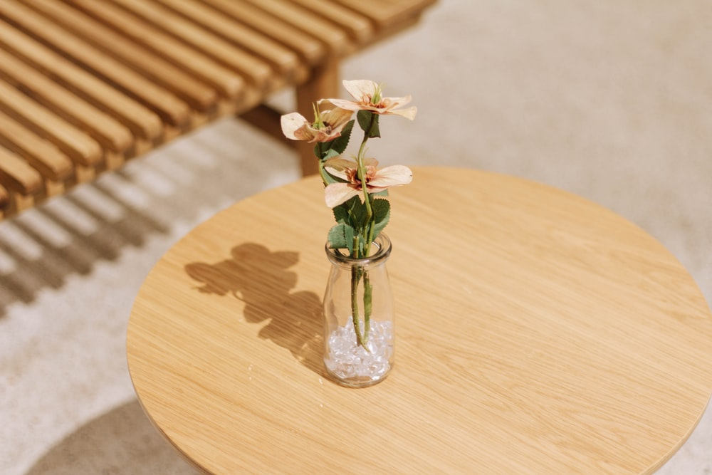 green plant in clear glass vase on brown wooden table