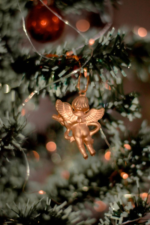 gold angel ornament on green christmas tree