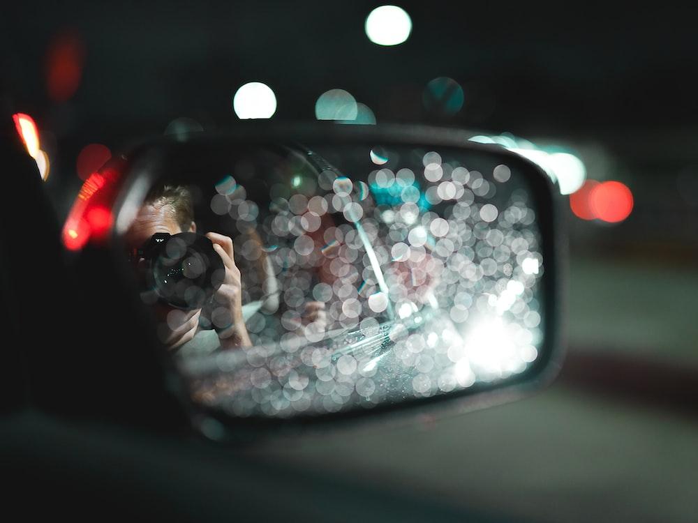 person in black sunglasses taking selfie on car side mirror