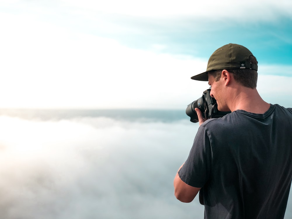 man in black shirt and black cap standing near foggy mountain during daytime