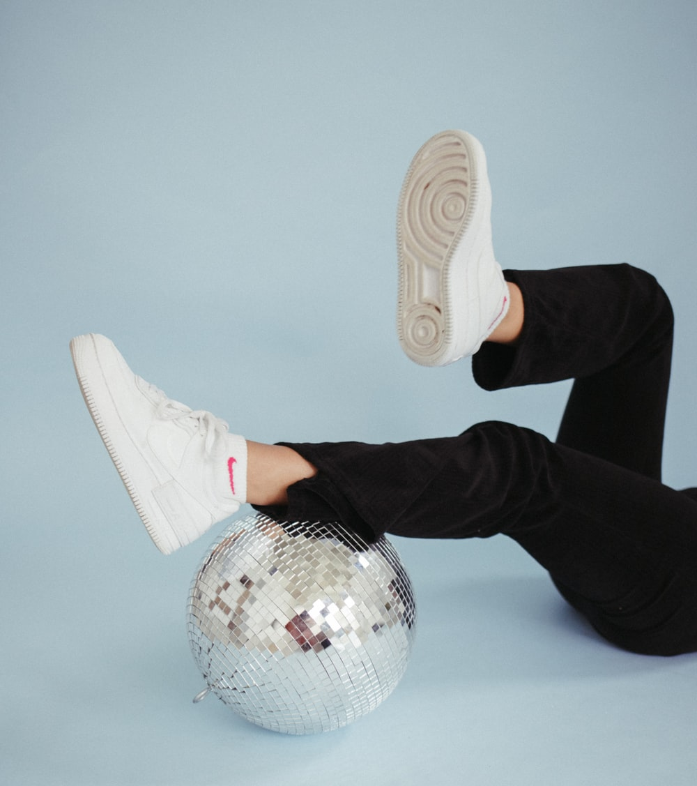 person in black pants wearing white sneakers