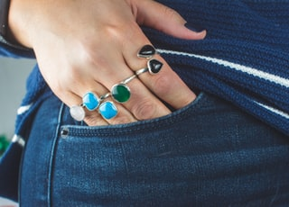 person wearing silver teal and green gemstone ring
