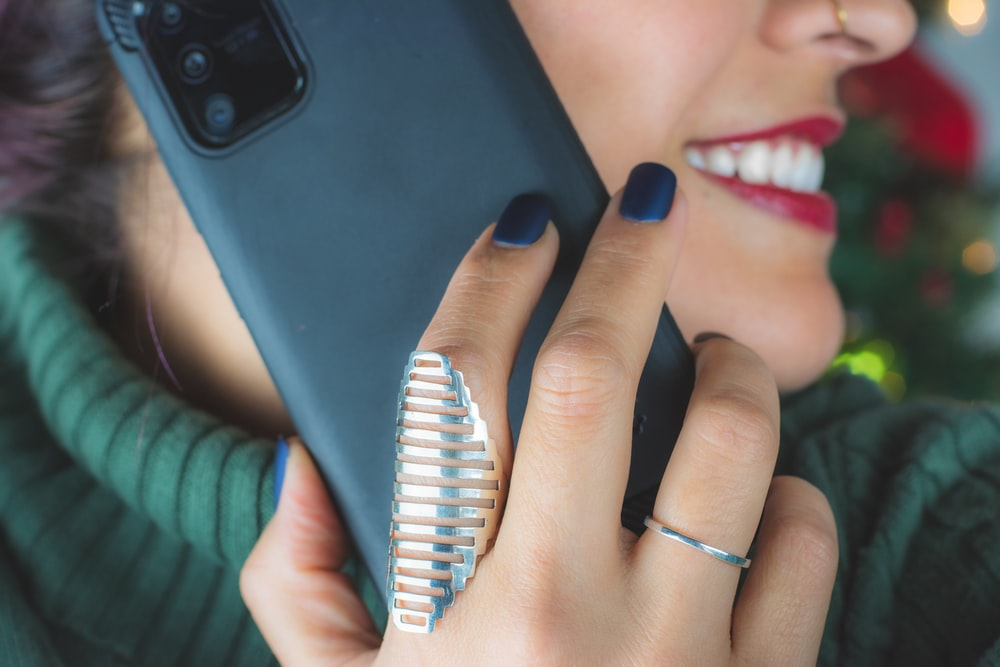 woman wearing silver ring holding black smartphone