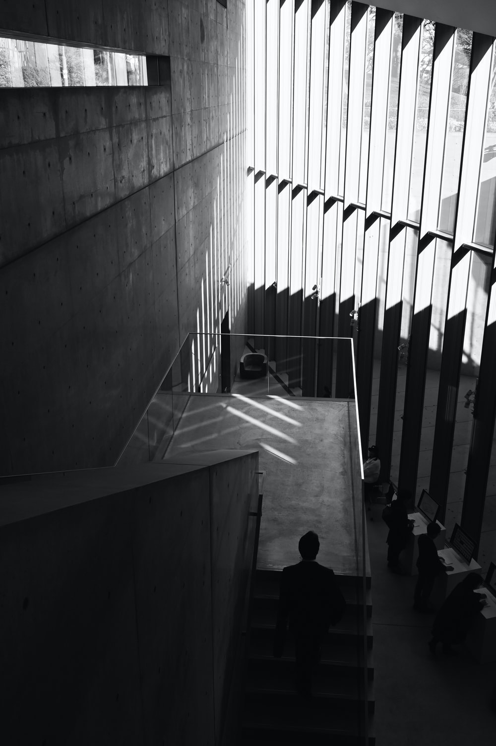 grayscale photo of person walking on stairs