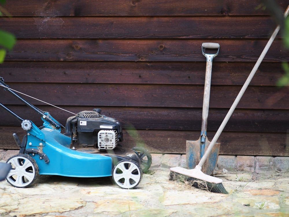 green and black push lawn mower beside brown wooden wall