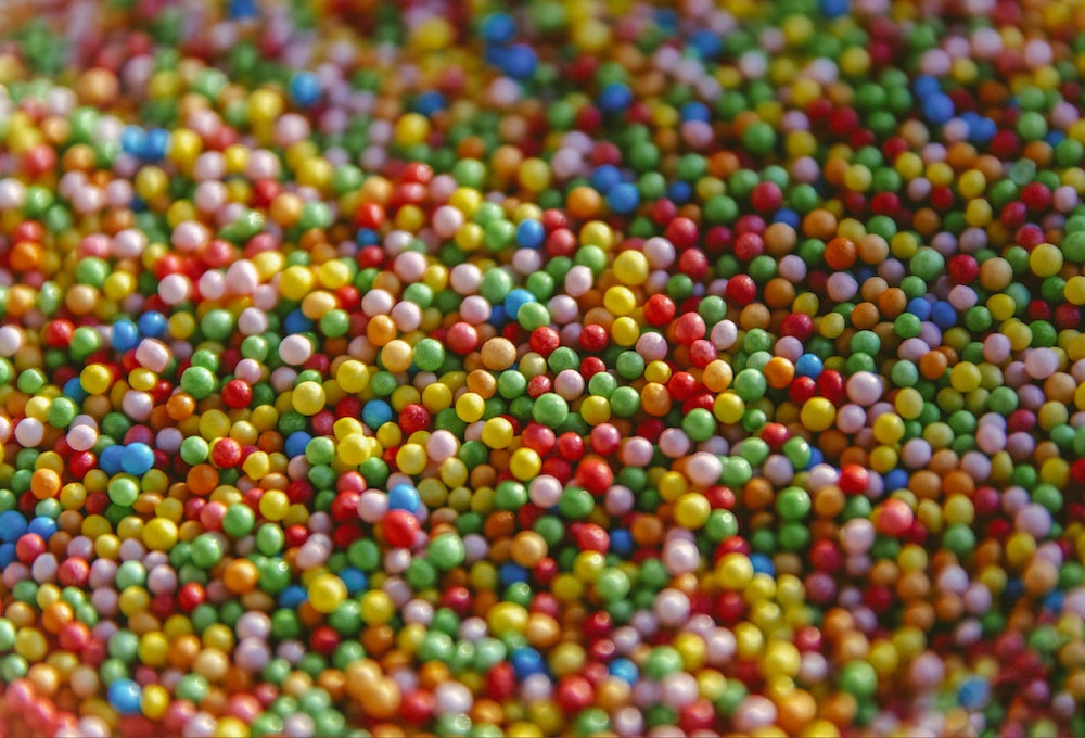 multi colored round beads on white surface