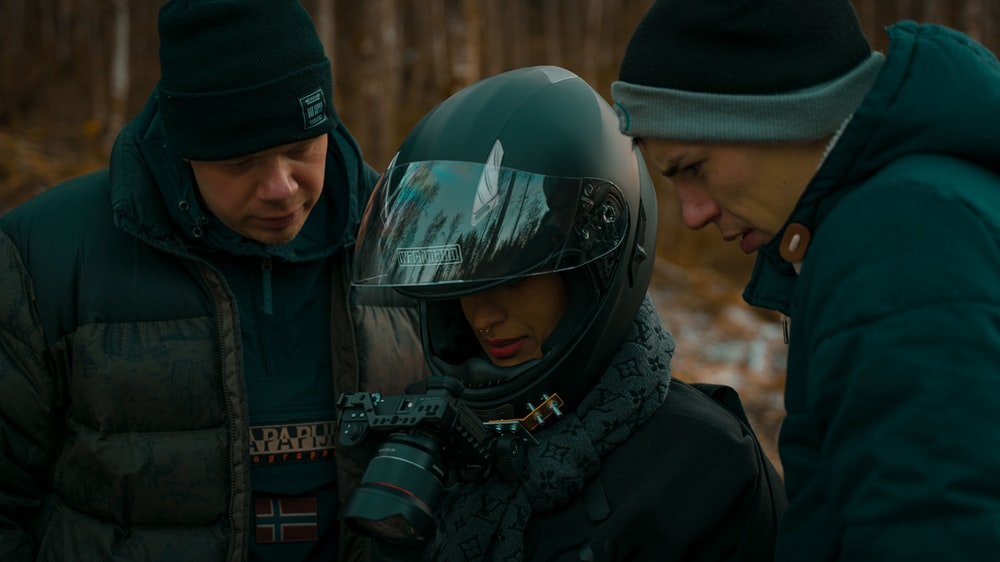 man in black jacket and helmet holding dslr camera