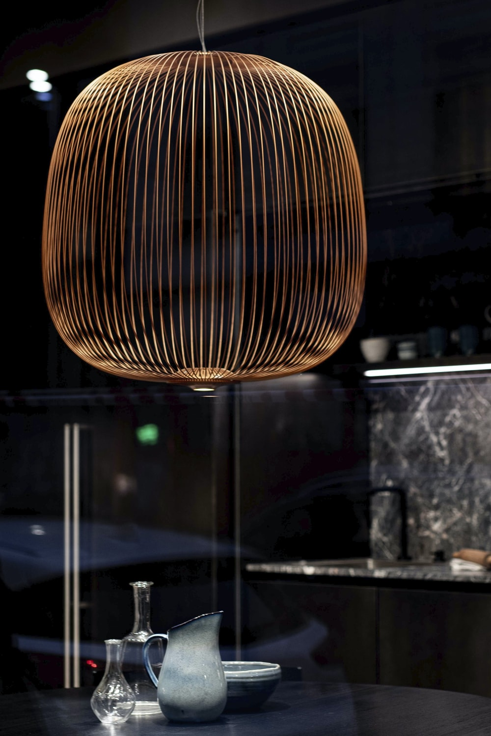brown round pendant lamp turned on in room