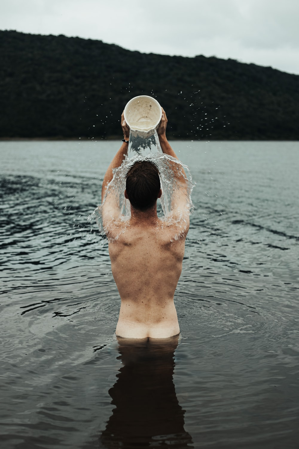 man in water holding white plastic bucket