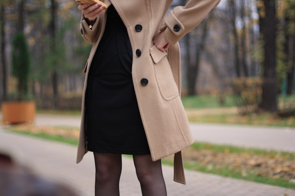 woman in brown coat standing on road during daytime