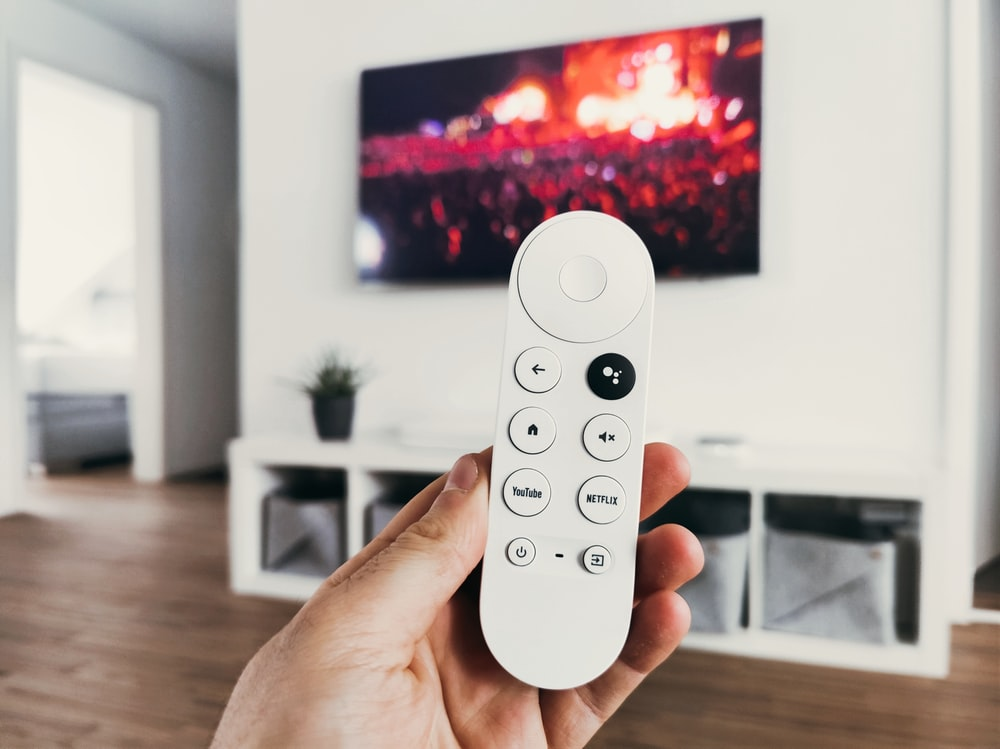person holding white remote control
