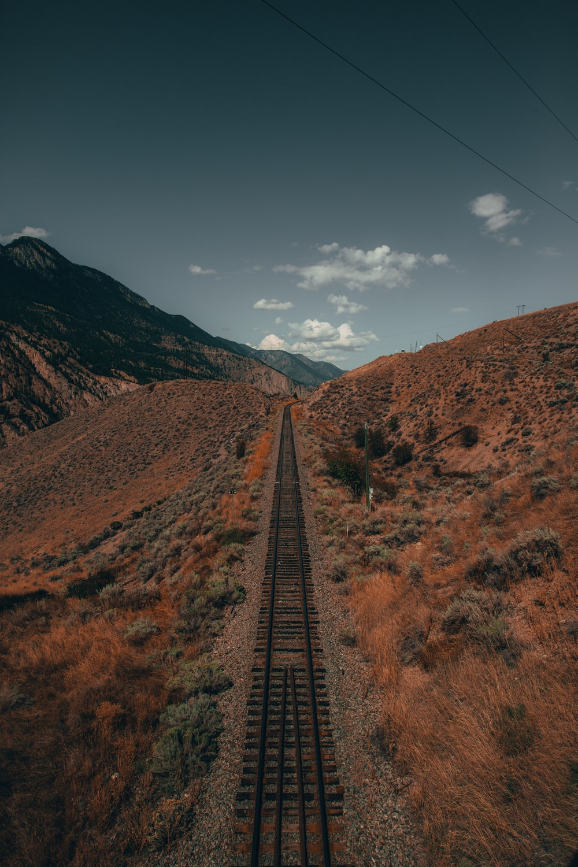 black metal train rail in between brown grass field during daytime