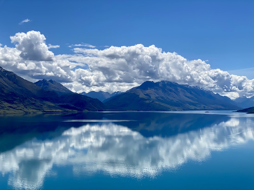 blue and white cloudy sky over lake