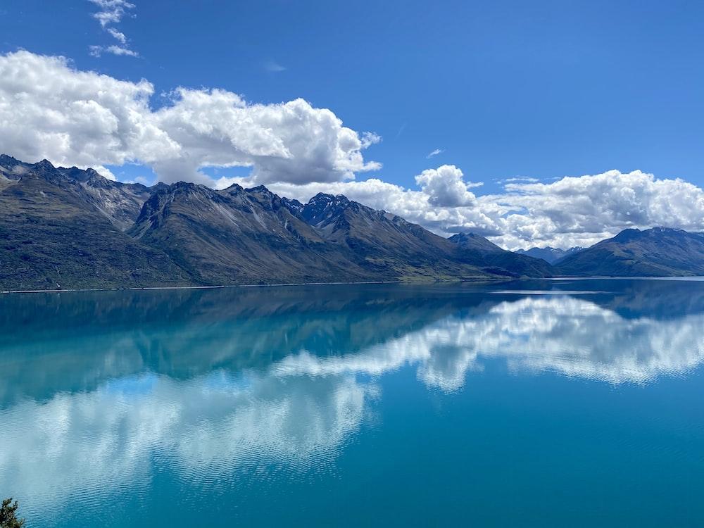 blue lake near brown mountain under blue sky during daytime