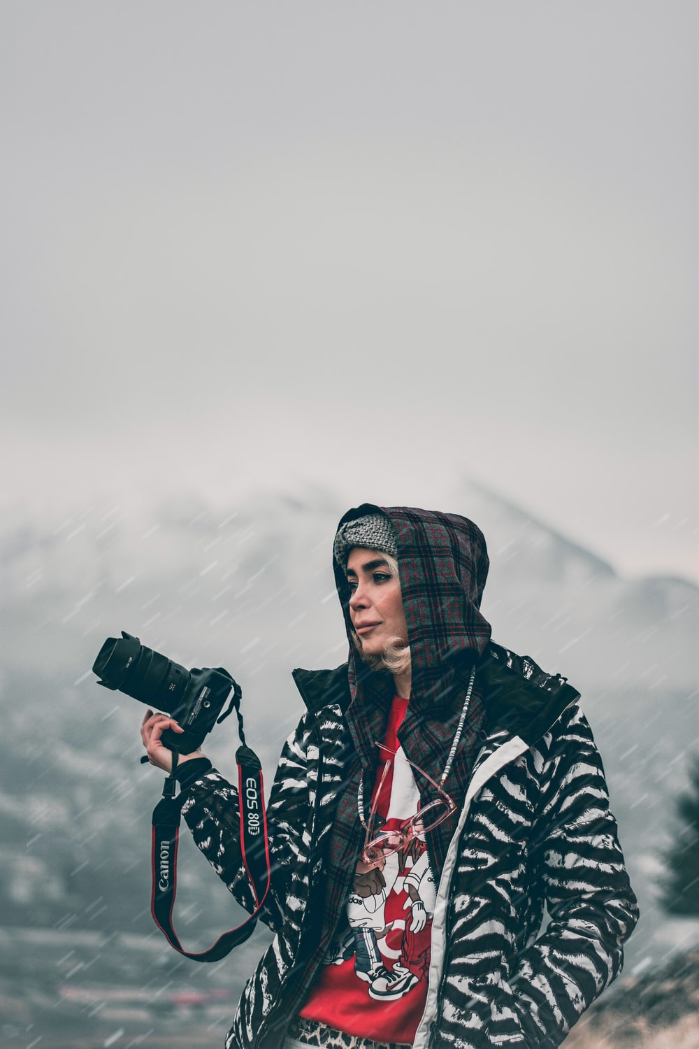 woman in black and white jacket holding black dslr camera
