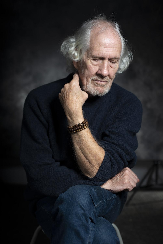 man in black long sleeve shirt sitting on chair