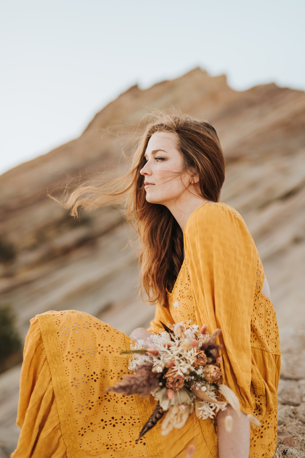 woman in yellow long sleeve shirt holding white flowers