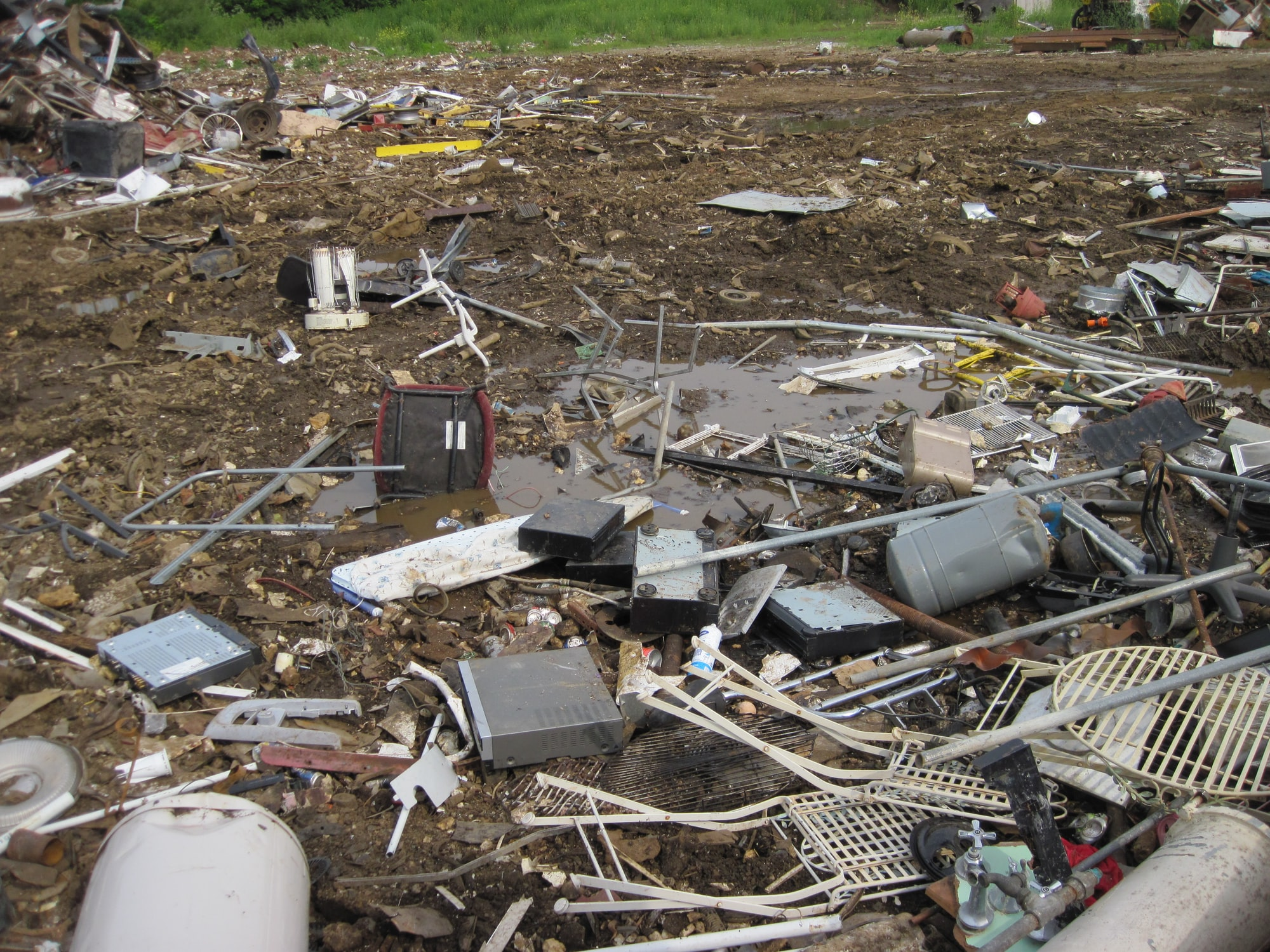 This is from a metal scrap yard in Richmond, Indiana.  There are clearly several VCRs or DVD players sitting in the mud in the foreground that should be handled as e-waste and not just scrap metal.   Electronics should be recycled through certificate e-waste processors, not metal scrap yards.