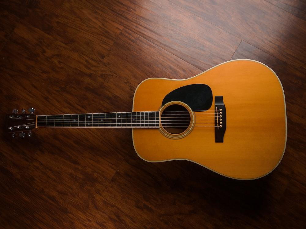 brown acoustic guitar on brown wooden floor