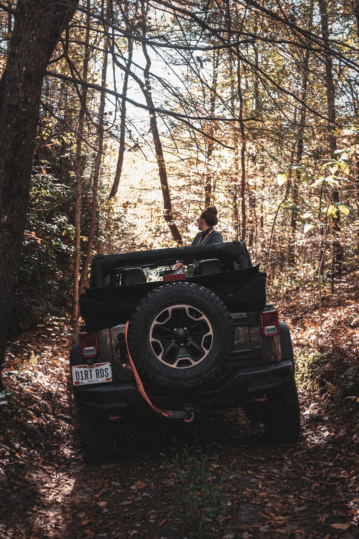 man in black jacket sitting on black jeep wrangler