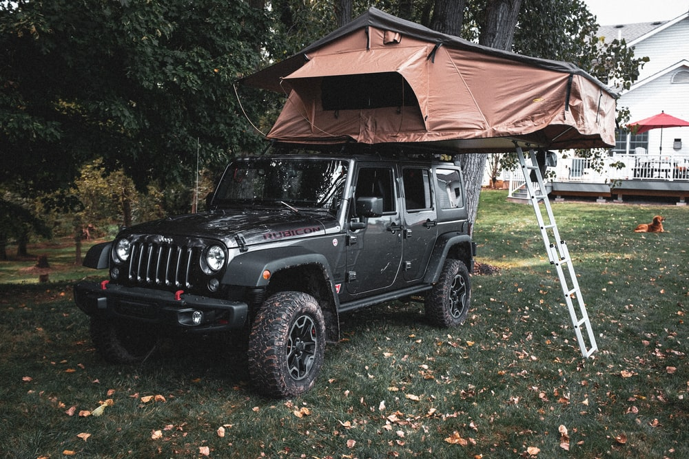 black jeep wrangler parked near brown wooden house during daytime