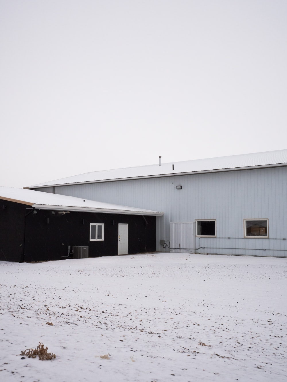 white and gray wooden house on snow covered ground