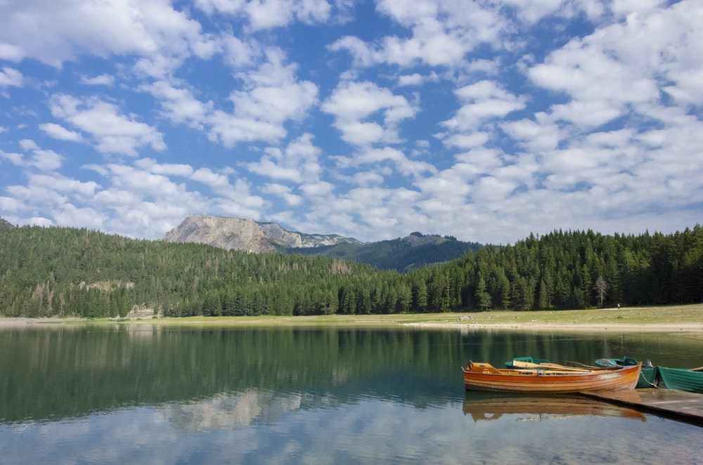 Brown Boat On Lake Near Green Trees And Mountain Under Blue And White Cloudy Sky During