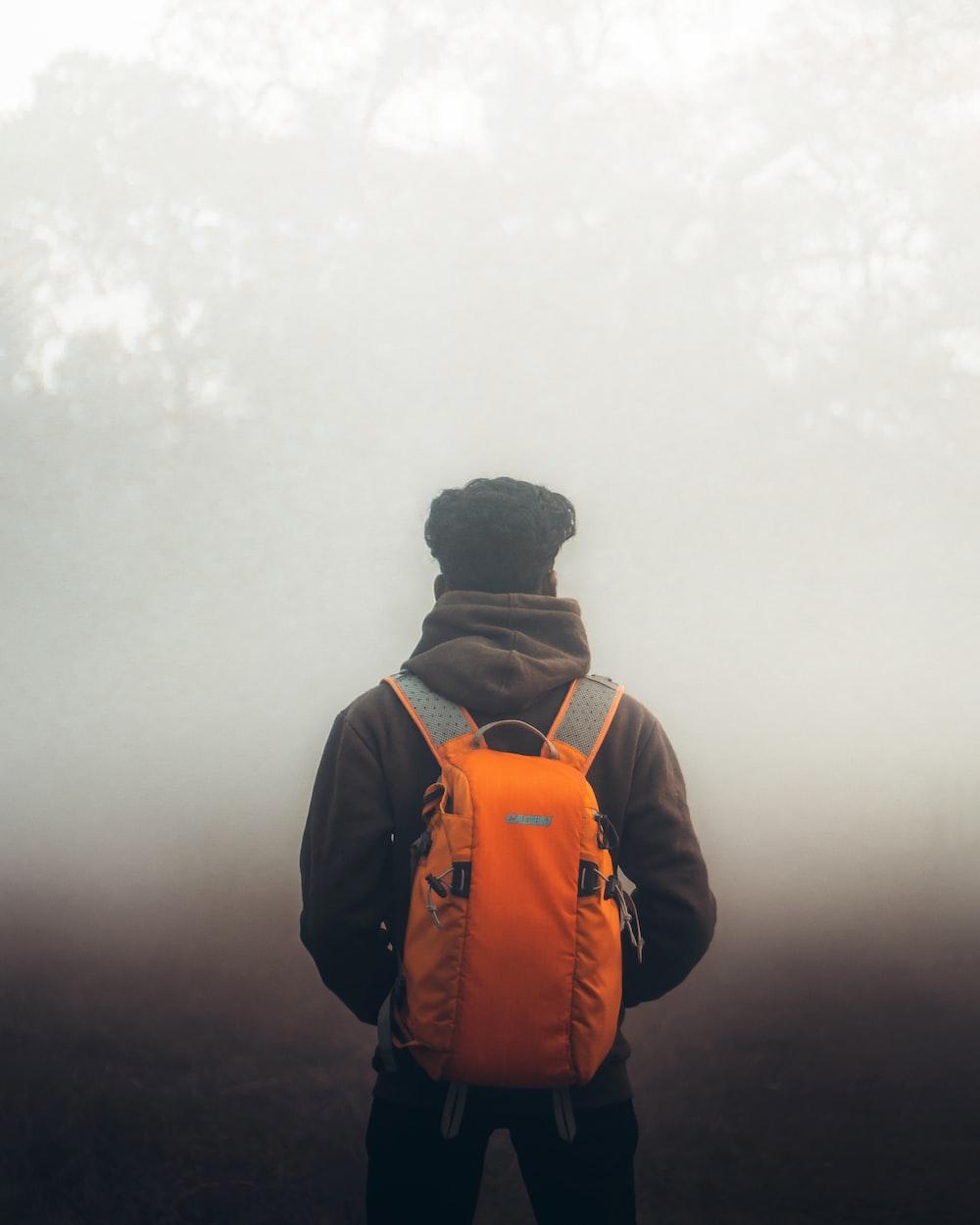 man in orange and black backpack