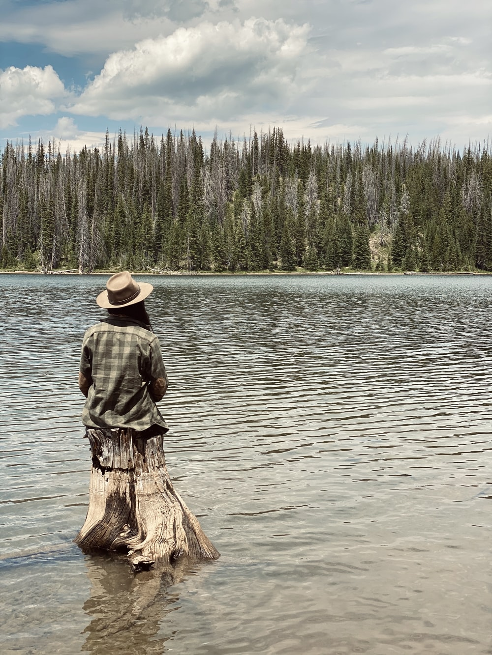 man in brown hat standing on brown wood log on body of water during daytime