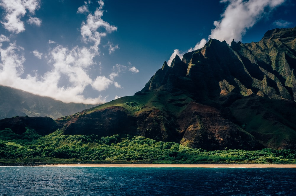 green and brown mountain beside blue sea under blue sky and white clouds during daytime