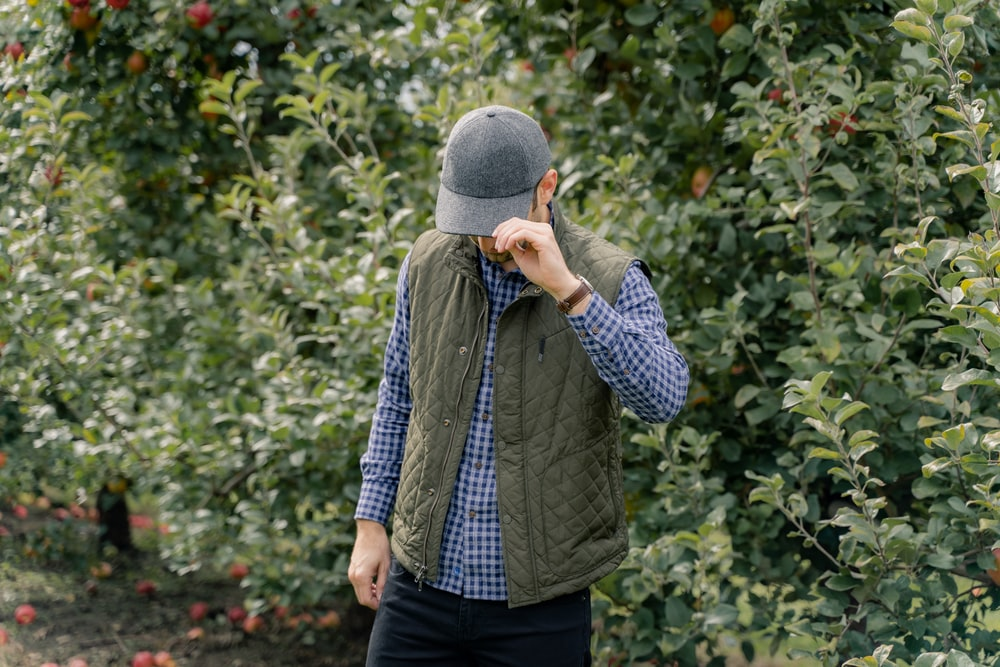 man in blue and white plaid dress shirt and gray knit cap standing near green plants