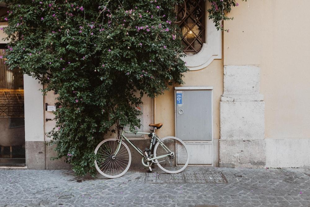 black city bike parked beside brown concrete building