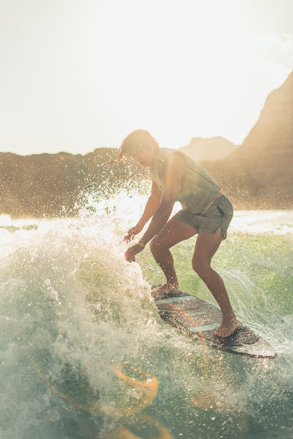 man in gray tank top and white shorts surfing on sea waves during daytime
