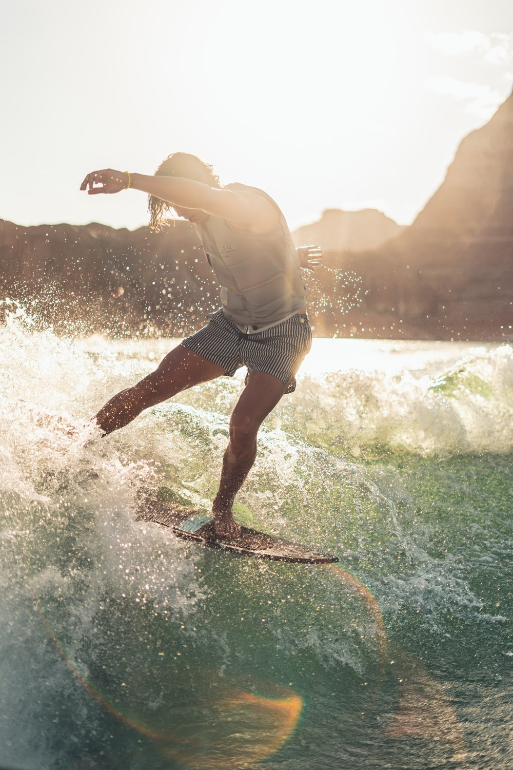 man in white tank top and blue shorts surfing on sea waves during daytime