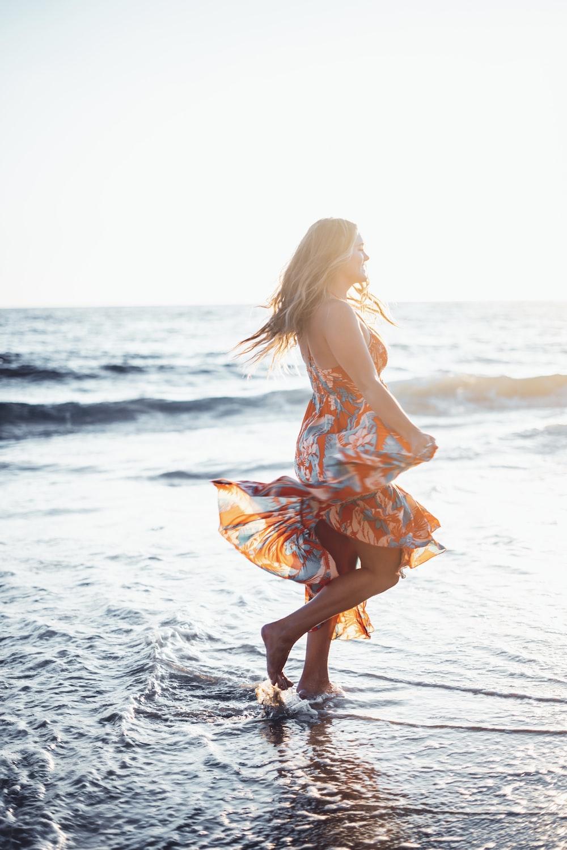 woman in orange dress walking on beach during daytime