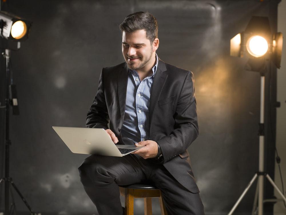 man in black suit jacket sitting on chair using macbook