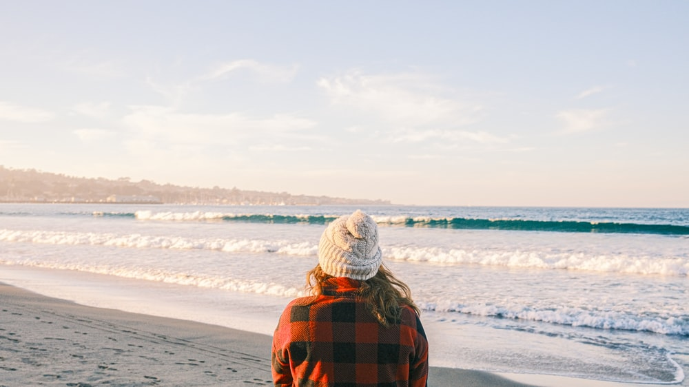 person in orange and black plaid hoodie standing on beach during daytime
