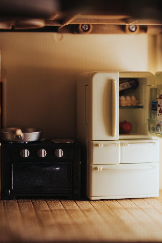 white top mount refrigerator beside black wooden cabinet