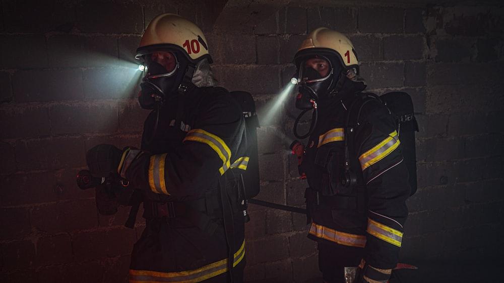 2 men in black and yellow suit wearing helmet
