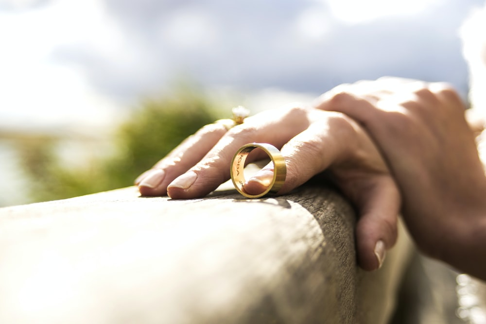 person holding gold wedding band