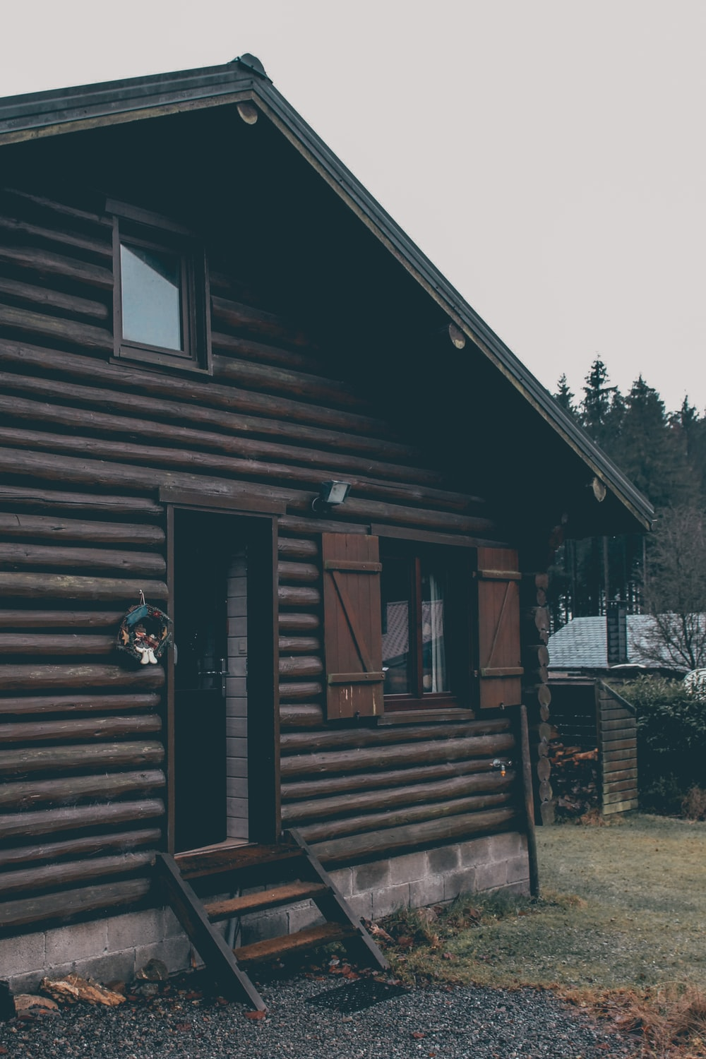 brown wooden house near green trees during daytime