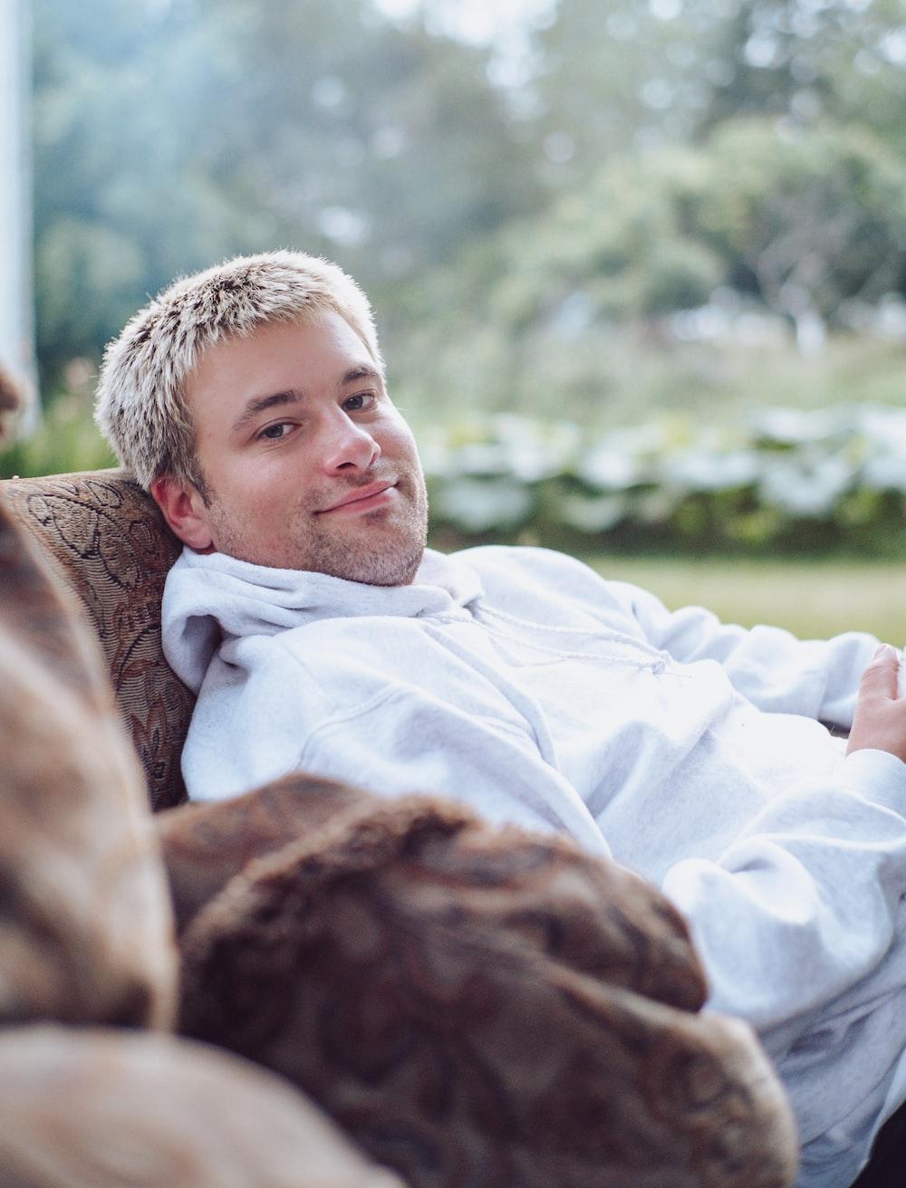man in white dress shirt lying on brown textile