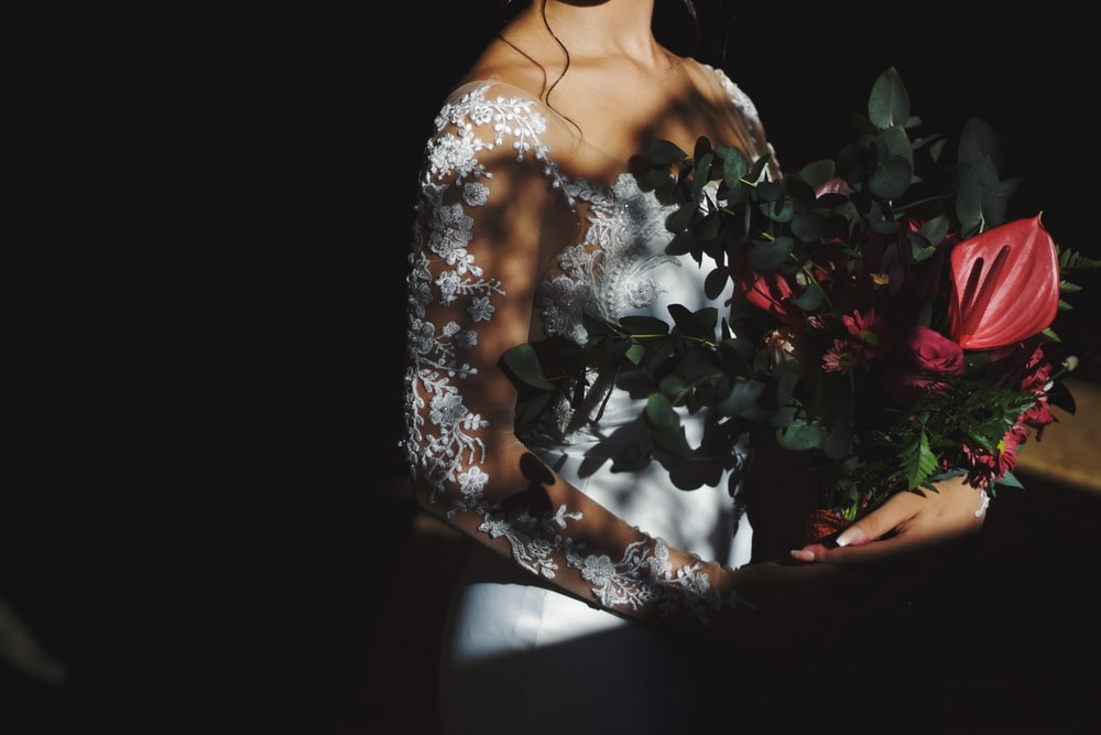 woman in white floral dress holding red rose bouquet