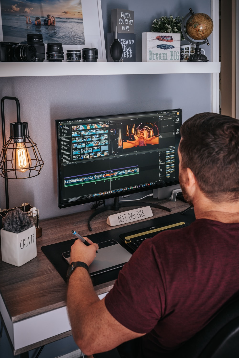 man in red shirt sitting in front of black flat screen computer monitor