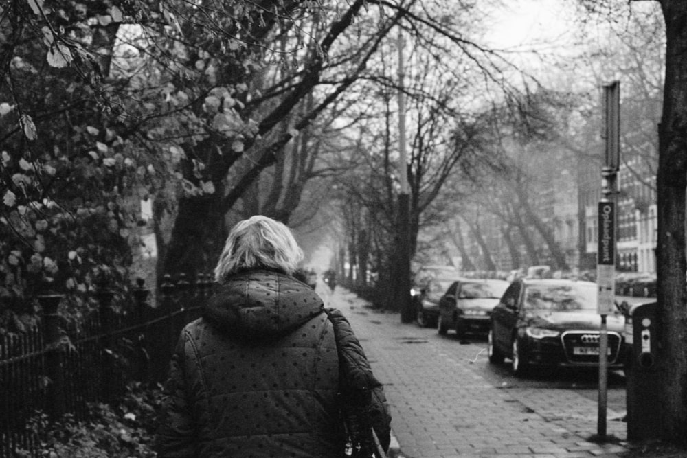 grayscale photo of woman in black jacket walking on sidewalk