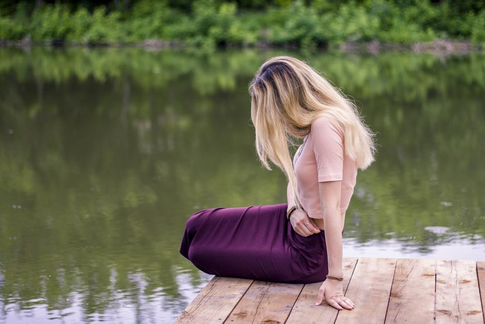 woman in purple dress sitting on wooden dock