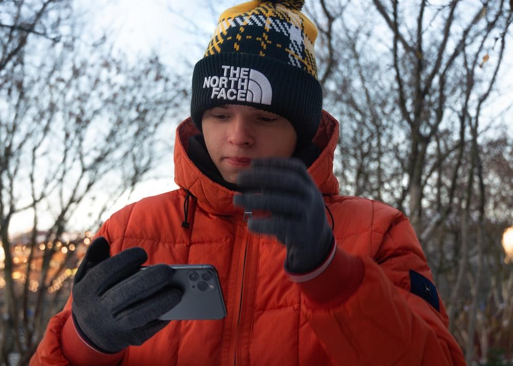 boy in orange jacket holding iphone