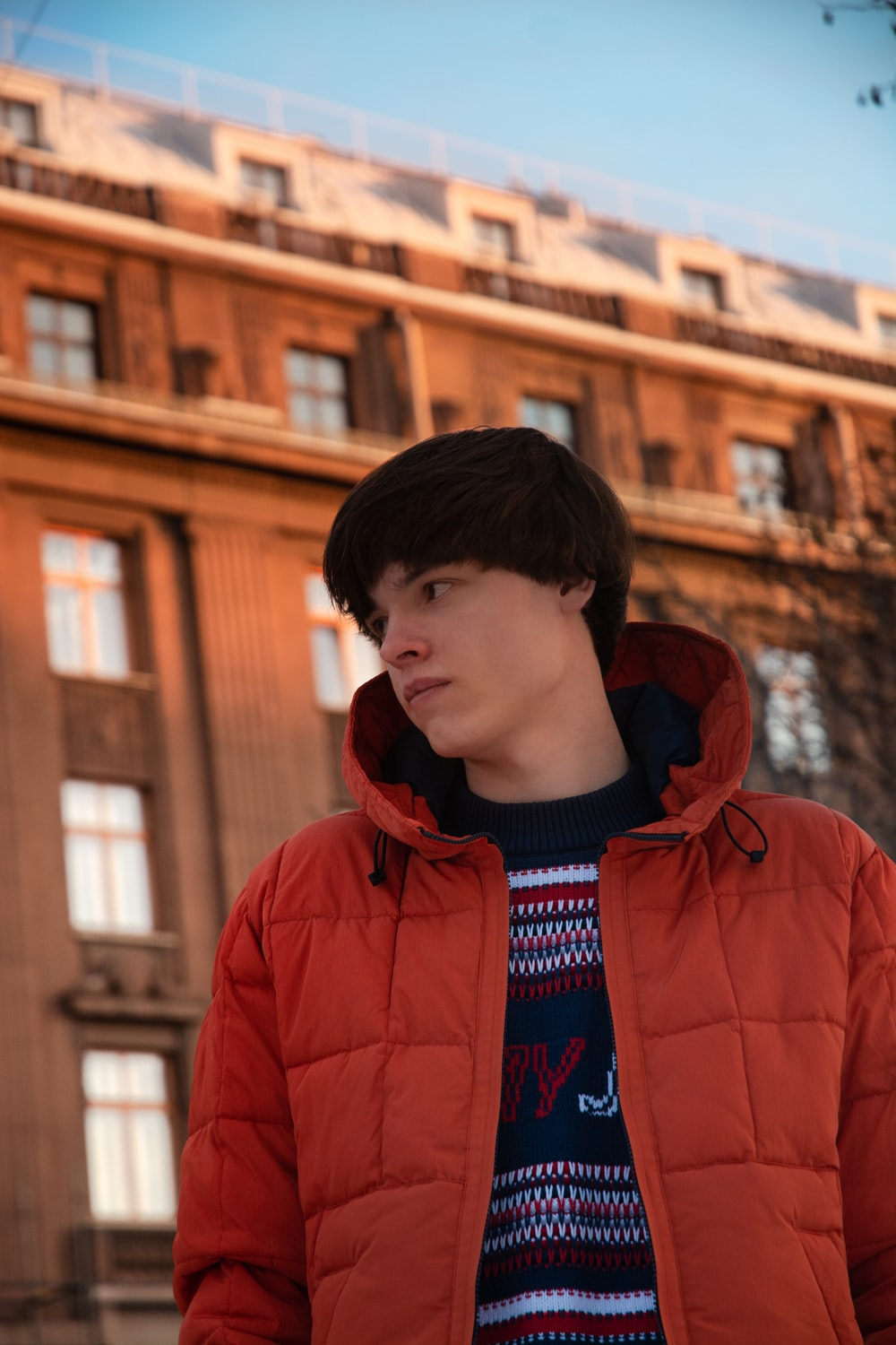 boy in red hoodie standing near brown building during daytime