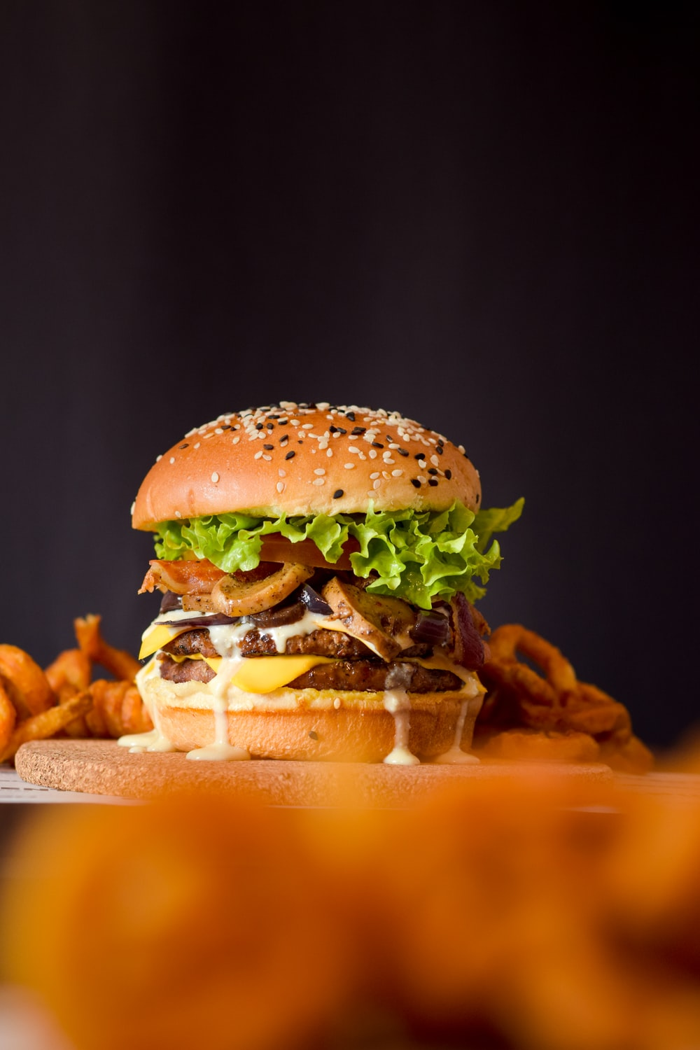 burger with lettuce and tomato on brown wooden tray